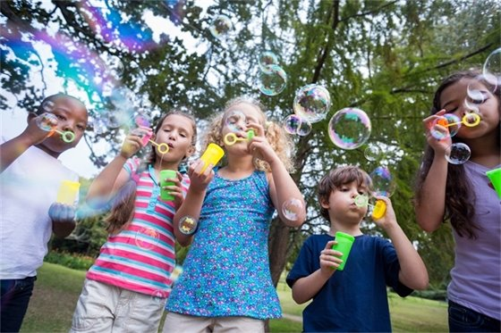 Image of a group of school-aged children blowing bubbles in a park.